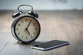 Black vintage alarm clock with phone on a wooden floor — Stock Photo