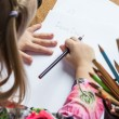 Small young girl drawing pictures with pencils — Stock Photo #71359387