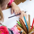 Small young girl drawing pictures with pencils — Stock Photo #71359415