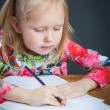 Small young girl drawing pictures with pencils — Stock Photo #71359417