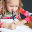 Small young girl drawing pictures with pencils — Stock Photo #71359421