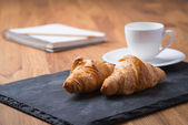 Two tasty french croissants with a cup of coffee and notebook — Stock Photo