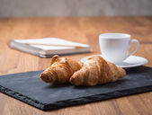 Two tasty french croissants with a cup of coffee and notebook — Stock fotografie