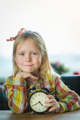 Young little hipster looking girl with alarm clock — Stock Photo