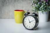 Old-Time Wecker auf einem weißen Tisch mit Blumen und Kaffeetasse — Stockfoto