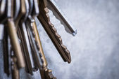 A bunch of old worn keys on the grey concrete wall — Stock Photo
