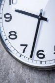 Kulaté nástěnné hodiny visí na šedou betonovou zeď — Stock fotografie