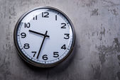 Round wall clock hanging on the grey concrete wall — Stock Photo