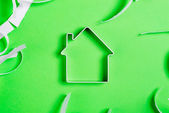 Metal house standing on a green surface with teared paper pieces — Stock Photo