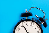 Old vintage alarm clock standing on the blue surface — Stock Photo