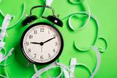 Old vintage alarm clock standing on the green surface with peaces of teared paper — Stock Photo