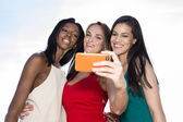 Portrait of three women taking selfies with a smartphone. Three friends posing for selfie, outdoors. — Stock Photo