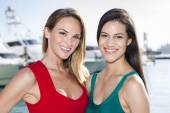 Two women posing in marina harbor, yachts on background. — Stock Photo