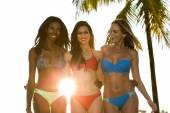 Three women in bikini walking, back lit. — Stock Photo