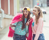Hipster girlfriends taking a selfie in urban city context - Concept of friendship and fun with new trends and technology - Best friends eternalizing the moment with modern smartphone — Stock Photo