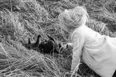 Young girl playing with a kitten in the grass. — Foto Stock