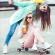 Hipster girlfriends taking a selfie in urban city context - Concept of friendship and fun with new trends and technology - Best friends eternalizing the moment with camera — Stock Photo #72870583