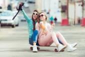 Fidanzate hipster prendendo un selfie nel contesto urbano della città - concetto di amicizia e divertimento con le nuove tendenze e tecnologia - migliori amici eternano il momento con la macchina fotografica — Foto Stock
