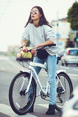 Colorful outdoor portrait of young pretty fashion model with bike. Young blonde sexy woman posing in summer. School girl style. — Stock Photo