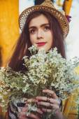 Hipster fashion girl in straw hat keep beauty flowers — Stock Photo