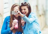 Fidanzate hipster prendendo un selfie nel contesto urbano della città - concetto di amicizia e divertimento con le nuove tendenze e tecnologia - migliori amici eternano il momento con smartphone moderno — Foto Stock