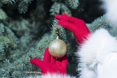 Red gloves hanging golden bauble — Stock Photo