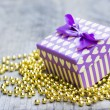 Purple gift box with yellow hearts upon golden pearls — Stock Photo #71643961