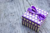 Purple gift box with yellow hearts greeting card — Stock Photo