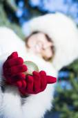 Smiling woman giving christmas tree ball wearing red gloves — Stock Photo