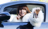 Smiling woman with car key — Stock Photo