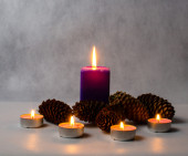 Candles of different sizes and colors, and cones on a bright bac — Stock Photo