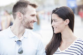 Funny couple laughing with a white perfect smile and looking each other outdoors with unfocused background — Stock Photo