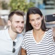 Happy couple taking a selfie photo with a smart phone in a restaurant terrace — Stock Photo #78550410