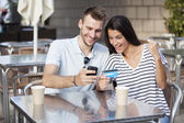 Couple buying online on holidays with a laptop and credit card on terrace bar — Stock Photo