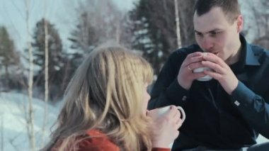 Young couple in love on a winter vacation enjoying the nature and drinking hot tea — Stock Video