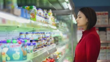 Young woman chooses the goods on a showcase — Vidéo