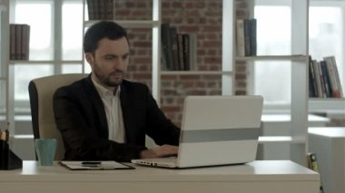 Businessmanworking on his computer in office while typing on keyboard — Stock Video