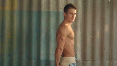 Forte uomo muscolare atletico bodybuilder, ragazzo sport mostrando i suoi muscoli maschili, in piedi di bac — Video Stock