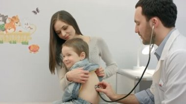 Doctor is examining boy with a stethoscope — Stock Video