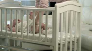 Mother caressing her cute baby girl sleeping in a cot — Stock Video