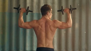 Young muscular man exercising with dumbbells — Stock Video