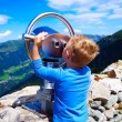 Little boy looking at the mountains through telescope — Stock Photo #71159713