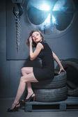 Beautiful woman tire, studio, sitting — Zdjęcie stockowe