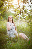 Pregnant sitting on the grass — Stock Photo