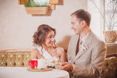 Bride and groom sitting in cafe — Stock Photo