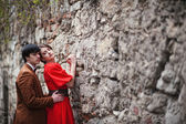 Young beautiful couple at the wall — Stock Photo