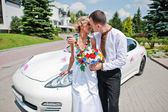 Wedding beautiful couple in traditional dress near exotic superc — Stock Photo