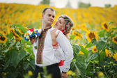 Wedding beautiful couple in traditional dress at the sunflower — Stock Photo