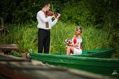 Wedding beautiful couple in traditional dress on the dock . Groo — Stock Photo