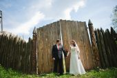 Wedding couple near old wooden fence holding hands — Stock Photo
